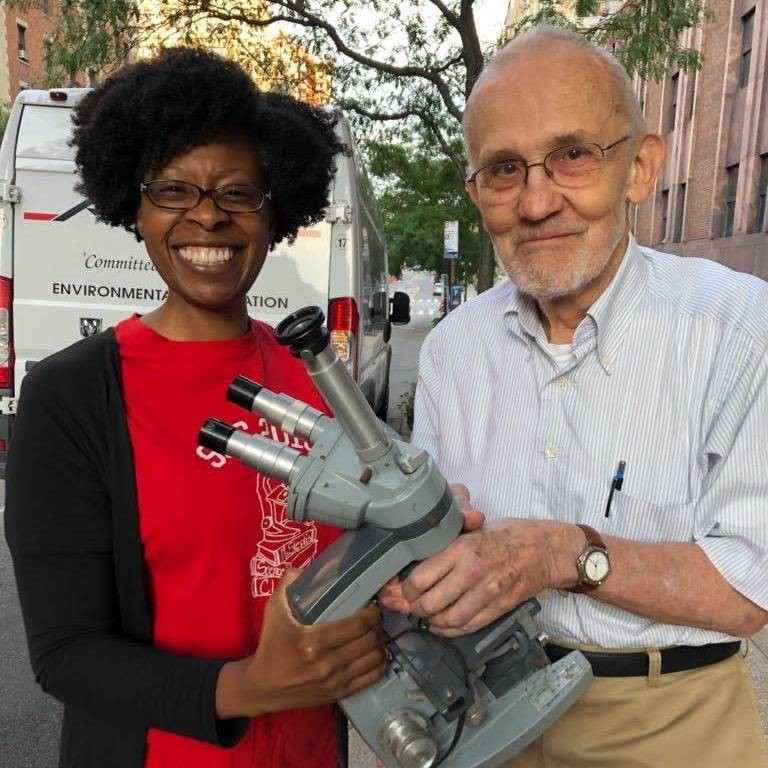 African American Woman in Red and Black Shirt poses with Elderly White Man - both holding a research microscope.